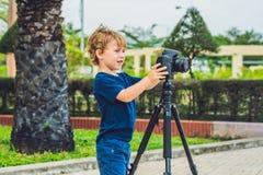 小孩男孩拍在一台照相机的照片在三脚架 库存照片