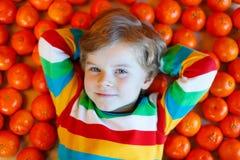 小孩男孩用健康橘子结果实 库存图片