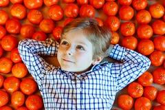 小孩男孩用健康橘子结果实 库存照片