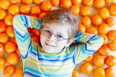 小孩男孩用健康橘子结果实 免版税库存照片