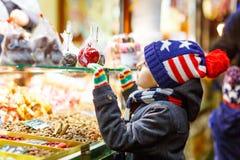 小孩男孩用姜饼和甜点在圣诞节市场上站立 库存照片