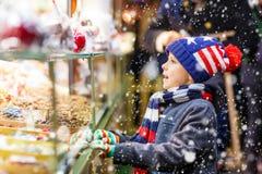 小孩男孩用姜饼和甜点在圣诞节市场上站立 图库摄影