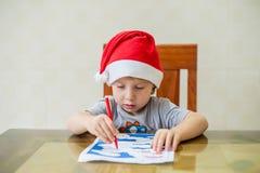 小孩男孩画毛毡在迷宫的笔道路 早期的发展概念 库存照片