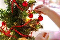 小孩的笔垂悬在一棵装饰的圣诞树的一个红色球 库存图片