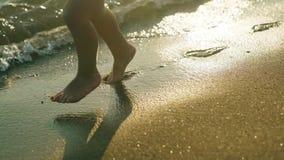 小孩的逗人喜爱的小腿特写镜头视图闪耀的蓝色海水的4k 股票录像