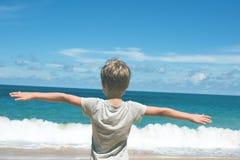 小孩立场蓝色天际海 库存照片