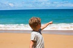 小孩立场蓝色海展示天际 库存图片