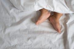小孩脚在白色床、板料和枕头上 图库摄影