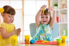 小孩获得乐趣与五颜六色的雕塑黏土一起在托儿 在家铸造创造性的孩子 儿童女孩 库存照片