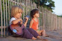 小孩获得在日落热带海滩的乐趣 库存照片