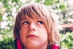 小孩贬小儿恼怒的面孔aexpression室外知觉连接 图库摄影
