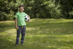 小孩足球运动员 有球的男孩在绿草 库存图片