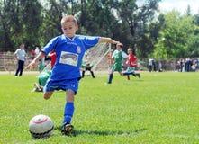 小孩踢橄榄球或足球 免版税库存照片