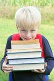 小孩运载的许多大重的教科书 库存图片