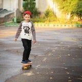 小孩骑马在滑板的公园 免版税库存照片