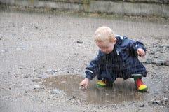 小孩,使用在水坑 免版税库存图片