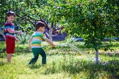 小孩,可爱的白肤金发的小孩男孩,浇灌植物, 免版税库存照片