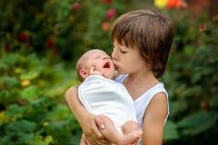 小孩,有一个新出生的兄弟的男孩在公园 图库摄影