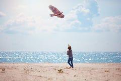 小孩,男孩飞行风筝在海边附近的晴朗的夏日 免版税图库摄影