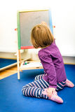 小孩画与在粉笔板的颜色白垩 免版税库存照片