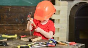 小安装工在车间 防护盔甲掩藏的男孩面孔 哄骗锤击钉子入木头 免版税库存照片