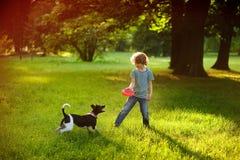 小家伙在公园训练一条狗 免版税图库摄影