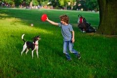 小家伙在公园训练一条狗 免版税库存照片