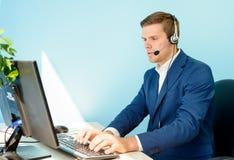 小家伙支持有运转在办公室的耳机的电话操作员 免版税库存照片