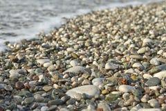 小小卵石和波浪 免版税库存照片