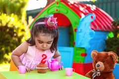 小小孩女孩在松饼的室外第二个生日聚会吹的蜡烛 免版税图库摄影
