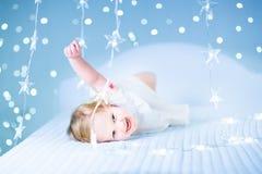 小小孩女孩在闪耀的蓝色光之间的床上 免版税库存图片
