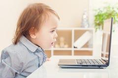 小小孩女孩惊奇了在她在她的膝上型计算机看的事 库存图片