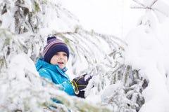 小小孩男孩获得与雪的乐趣户外在美丽的wi 免版税库存图片