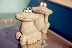 小小雕象在一个空的游泳池的边缘的逗人喜爱的两只青蛙 秋天概念查出的白色 图库摄影