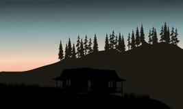 小屋剪影有云杉的背景 库存照片