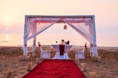小屋和浪漫晚餐设置在海滩 免版税库存照片