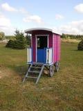小屋在有树和flowersrs的公园 免版税库存图片