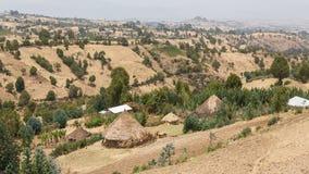 在小山的村庄小屋 库存照片