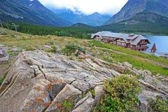小屋在积雪覆盖的山下坐 免版税库存图片