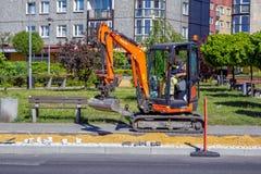 小履带牵引装置挖掘机在自行车道建筑运转 免版税库存照片