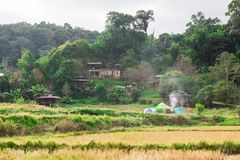小山上升从烹调的部落村庄和烟 图库摄影