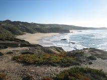 小山和沙丘围拢的偏僻的海滩 免版税库存照片
