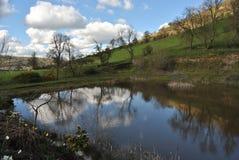 小山和湖或者水库,多云天空在水中,威尔士植物群,纯净的自然的反射在春天,萨罗普郡小山,威尔士英国 库存图片