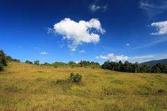 小山和蓝色多云天空 库存图片