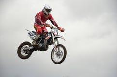 小山在竟赛者的飞跃摩托车 库存图片