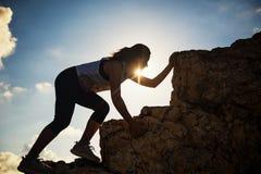 小山山顶的女性远足者在日落 免版税图库摄影