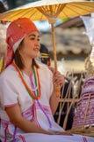 小山拿着在游行的部落女孩红色纸伞 免版税库存图片