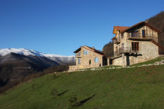 小山的两个石房子在多雪的山背景,明白蓝天,水平 库存图片