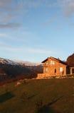小山的偏僻的石房子在多雪的山背景,在日出,垂直 免版税库存图片