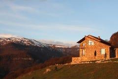 小山的偏僻的石房子在多雪的山背景,在日出,水平 库存照片